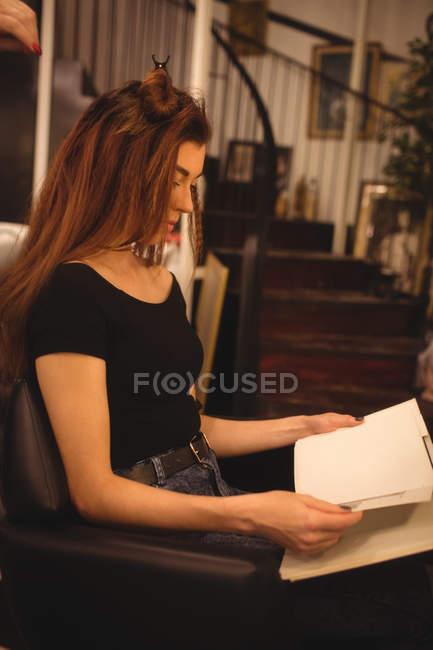 Женщина читает журнал во время укладки волос в салоне волосы — стоковое фото