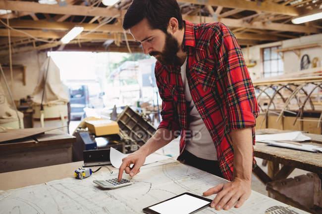 Людина за допомогою цифрових планшетів і калькулятор у верфі — стокове фото
