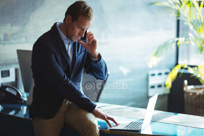 Businessman talking on mobile phone while using laptop in office — Stock Photo