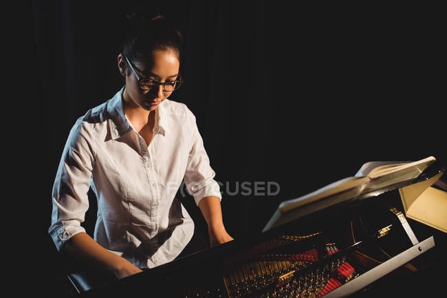 Beautiful woman playing a piano in music studio — Stock Photo