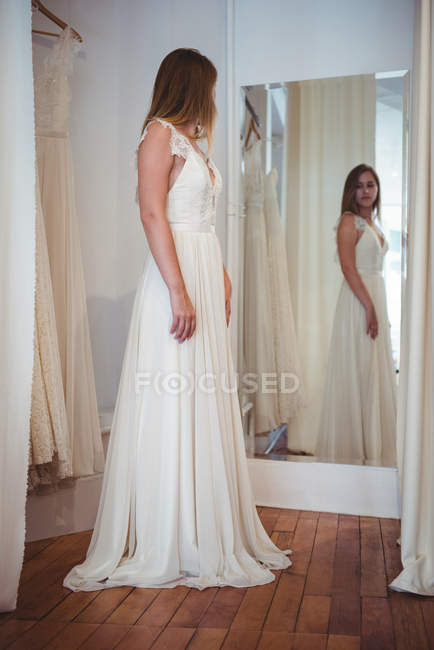 Beautiful woman trying on wedding dress in a shop in studio — Stock Photo