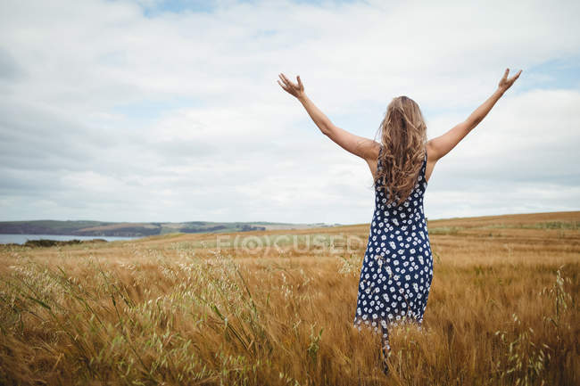 Rear view woman standing with arms outstretched in field — Stock Photo