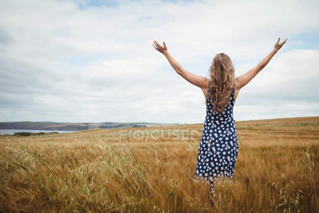 Frau steht mit ausgestreckten Armen im Feld — Stockfoto