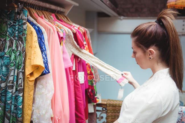 Choisir un vêtement sur cintre au magasin de vêtements de femme — Photo de stock
