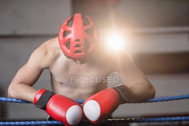 Сорочки боксера в захисних шоломи боксерські спираючись на тросах боксерський ринг в фітнес-студія — стокове фото