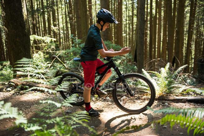 Ciclista masculino usando telefone celular na floresta à luz do sol — Fotografia de Stock