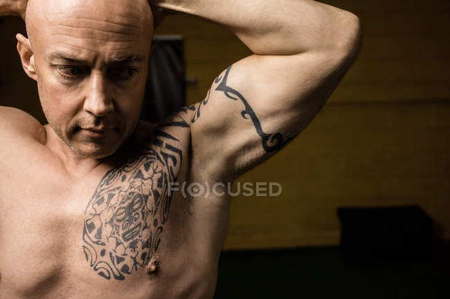 Close up of tattooed shirtless thai boxer posing in gym — Stock Photo