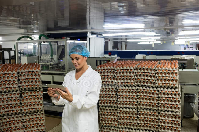 Female worker using digital tablet in egg factory — Stock Photo