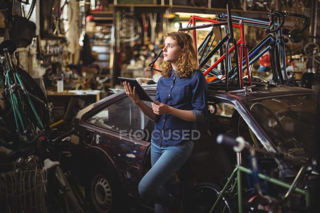 Механік, використовуючи цифровий планшетний під час ремонту велосипедів в майстерні — стокове фото