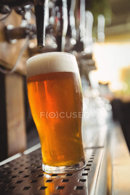 Close-up of beer glass with froth in a bar — Stock Photo