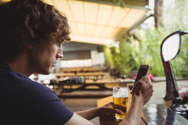 Hombre con vaso de cerveza usando teléfono móvil en el mostrador en el bar - foto de stock