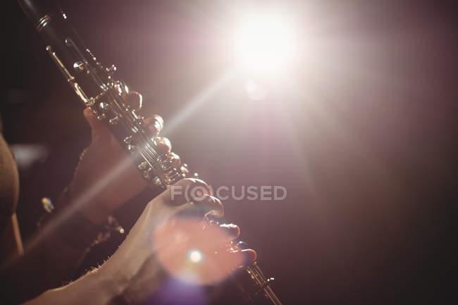 Женщина играет на кларнете в музыкальной школе — стоковое фото
