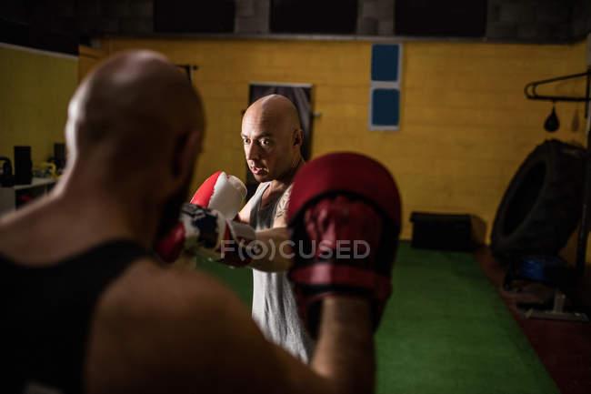 Foco seletivo de dois boxeadores tailandeses praticando boxe no ginásio — Fotografia de Stock