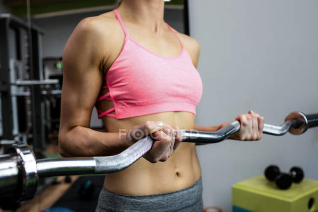 Mid-section of woman working out with barbell at gym — Stock Photo