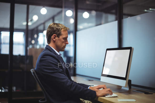 Businessman using desktop pc at desk in office — Stock Photo