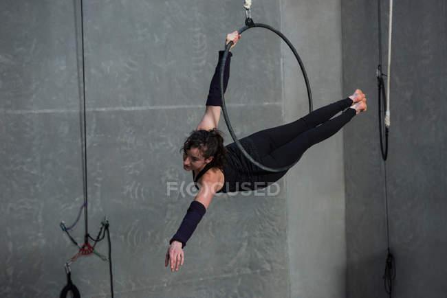 Female gymnast performing gymnastics on hoop in fitness studio — Stock Photo