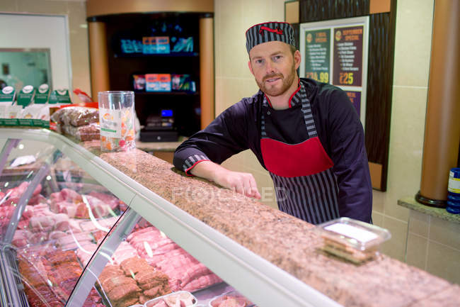 Portrait of butcher leaning on counter at butchers shop — Stock Photo