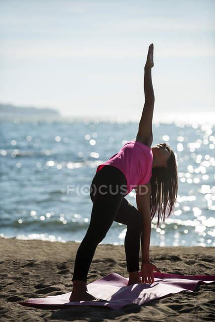 Женщина практикует йогу на пляже в солнечный день — стоковое фото