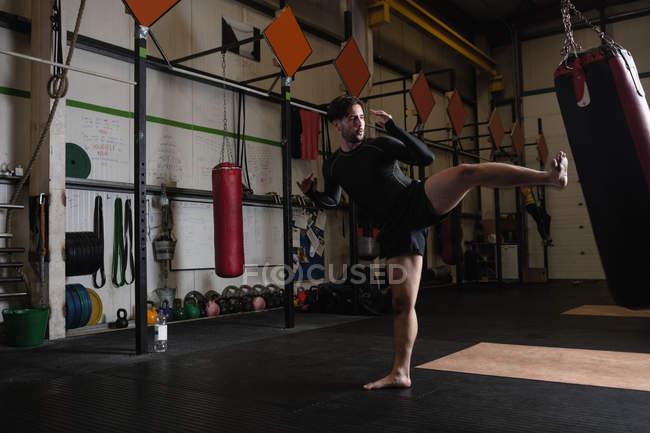 Seitenansicht eines Boxers beim Boxen mit Boxsack im Fitnessstudio — Stockfoto
