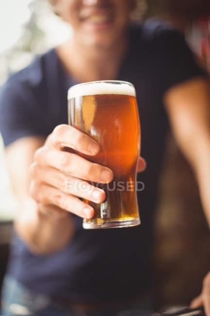 Крупний чоловік тримає скляні пивом у барі — стокове фото