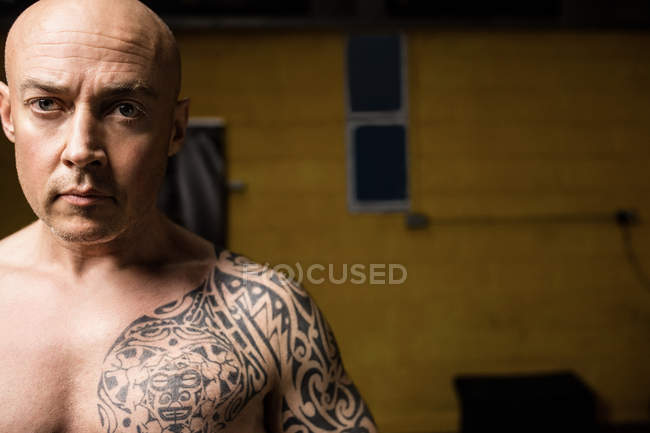 Tattooed shirtless thai boxer posing in gym — Stock Photo
