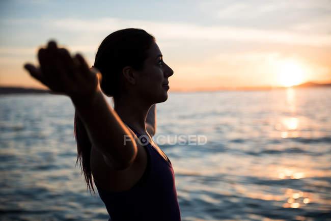 Vue latérale de la femme attrayante exécutant le yoga sur la plage pendant le coucher du soleil — Photo de stock