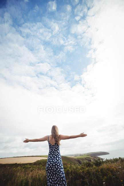 Vue arrière femme debout avec les bras tendus sur la falaise sur la mer — Photo de stock