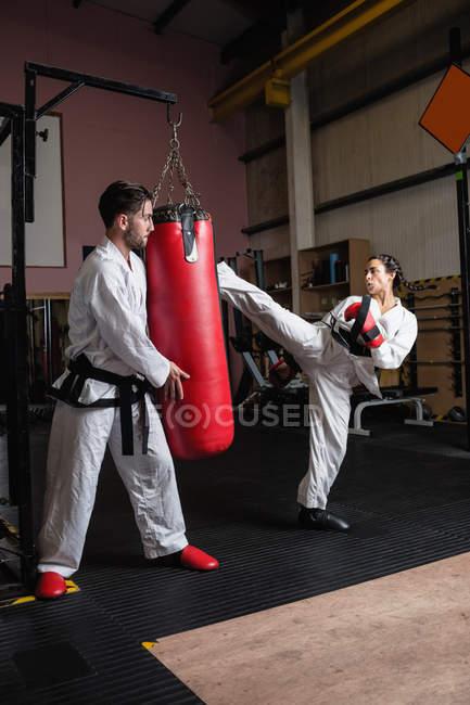 Mann und Frau üben Karate mit Boxsack im Studio — Stockfoto