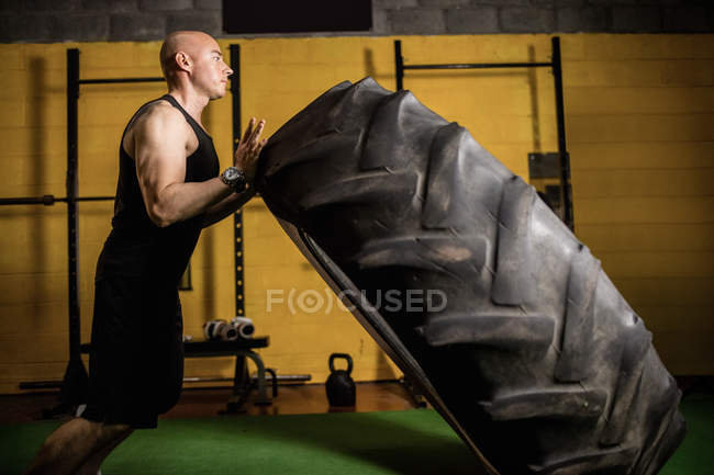 Side view of handsome sportsman lifting heavy tire in gym — Stock Photo