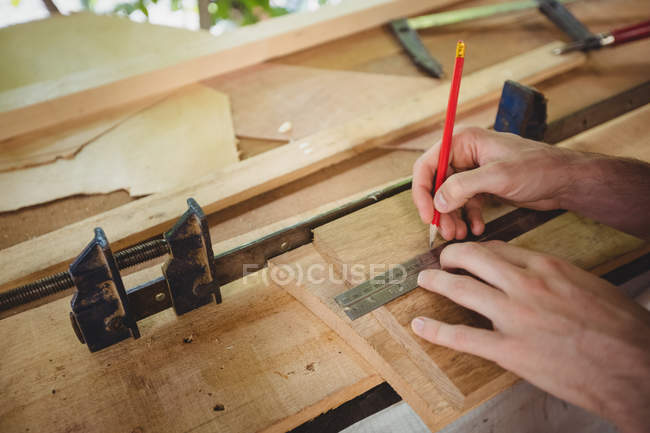 Mann misst Holzplanke in Bootswerft — Stockfoto