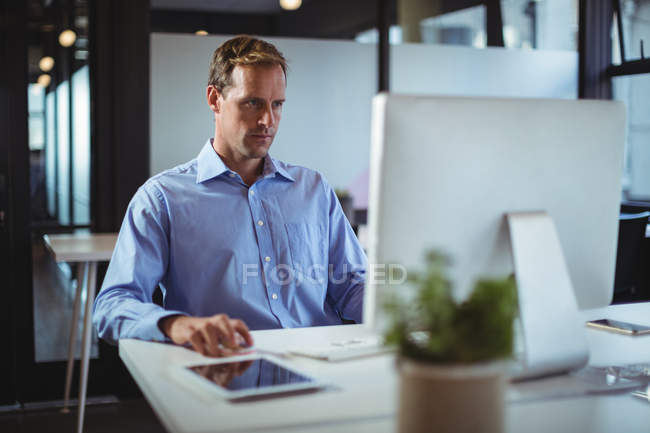 Businessman using desktop pc in office — Stock Photo