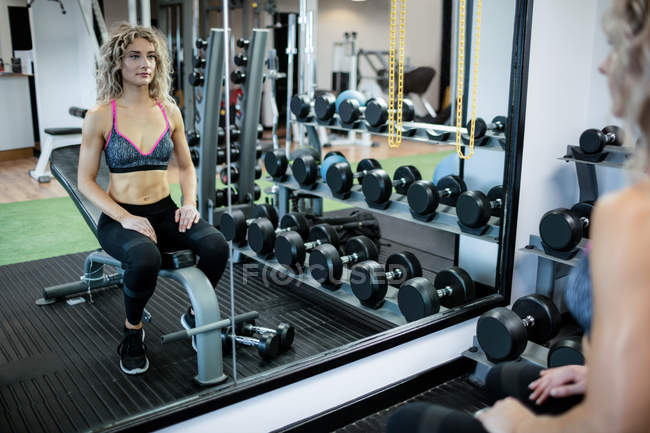 Reflection of beautiful woman working out in gym — Stock Photo