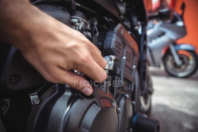 Рука механік закриття масляний бак моторного велосипеда на семінарі — стокове фото