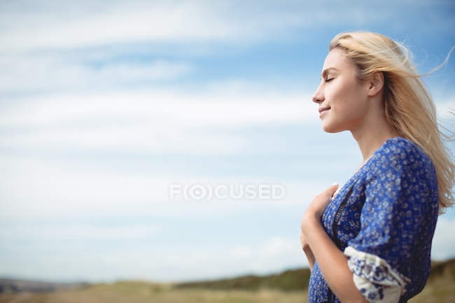 Side view of blonde woman standing in field with closed eyes — Stock Photo