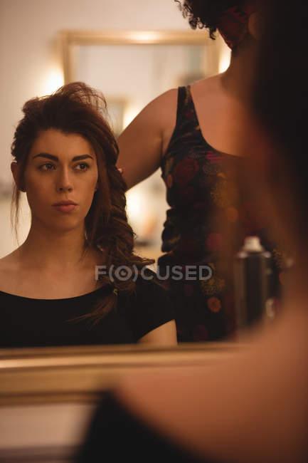 Отражение красивая женщина на зеркало с новой прической в салоне — стоковое фото