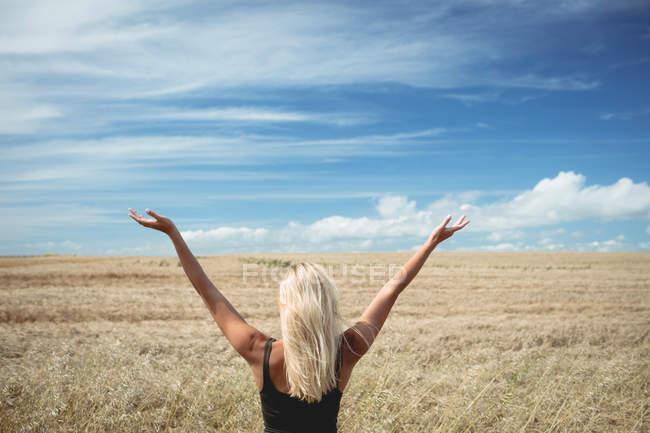 Вид сзади на блондинку, стоящую в поле с распростертыми объятиями — стоковое фото