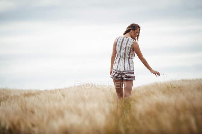 Frau berührt Weizen auf Feld an sonnigem Tag auf dem Land — Stockfoto