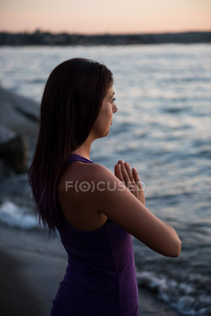 Beautiful woman meditating on beach at evening — Stock Photo