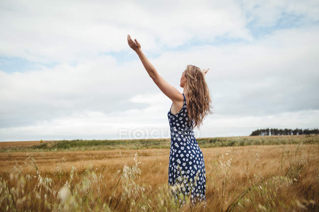 Rear view woman standing with outstretched arms in field — Stock Photo