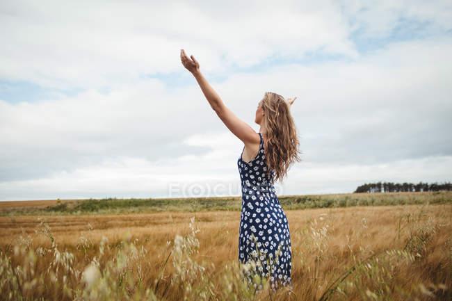 Vista posteriore donna in piedi con le braccia tese in campo — Foto stock