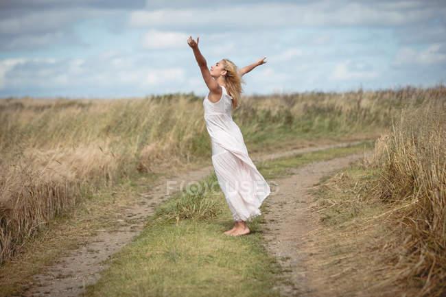 Vista laterale della donna bionda in piedi in campo a braccia aperte — Foto stock