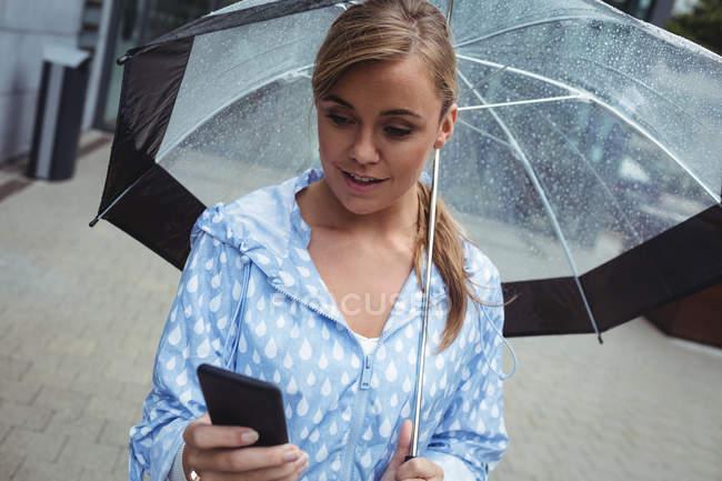 Belle femme tenant parapluie tout en utilisant smartphone pendant la saison des pluies — Photo de stock