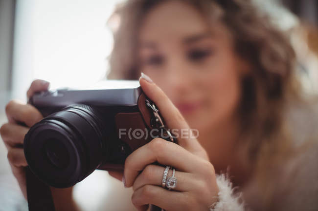 Woman looking at digital camera in bedroom at home — Stock Photo