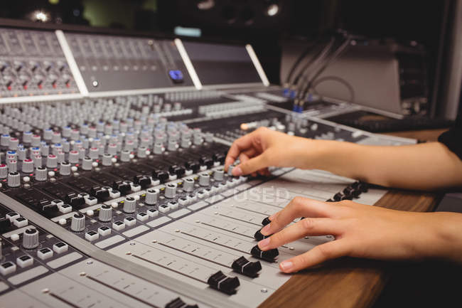 Hands of a female student using sound mixer in a studio — Stock Photo