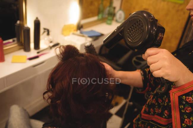 Pelo estilista brushing pelo de la mujer en un salón profesional - foto de stock