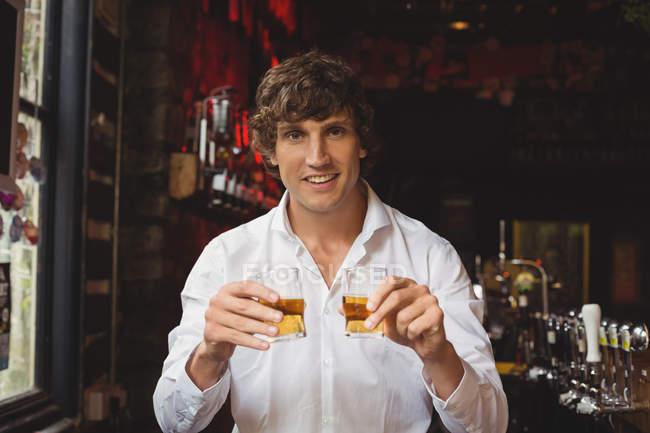 Portrait of bartender holding whisky shot glasses at bar counter in bar — Stock Photo