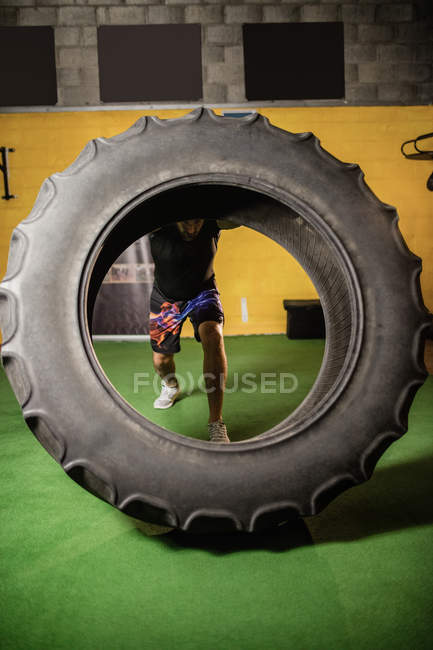 Strong sportsman lifting heavy tire in gym — Stock Photo