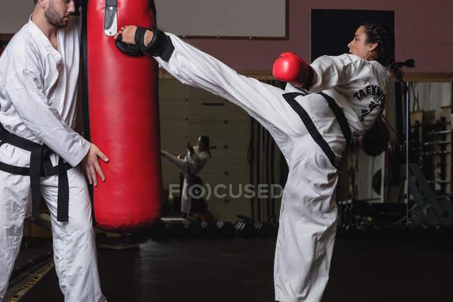 Seitenansicht der Sportlerin und des Sportlers beim Karate mit Boxsack im Studio — Stockfoto