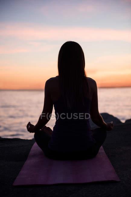 Задний вид женщины, практикующей йогу на пляже в сумерках — стоковое фото