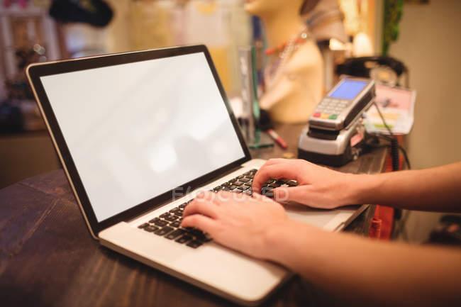 Manos de personal femenino usando un portátil en un mostrador en la tienda boutique - foto de stock